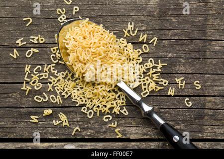 Alfabeto di pasta a cucchiaio sul vecchio tavolo in legno Foto Stock