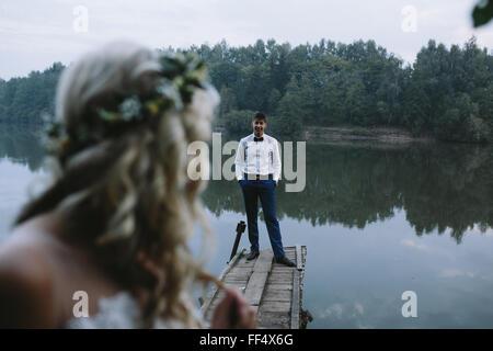 Coppie in viaggio di nozze sul vecchio molo in legno Foto Stock