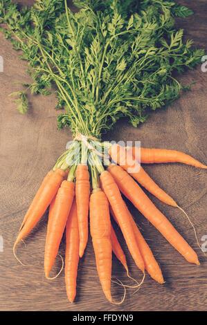 Un mazzetto di carote fresche in legno marrone scuro e tabella Foto Stock