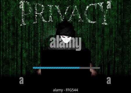 Un uomo mascherato in un laptop che simboleggia i pericoli di Internet. Foto Stock
