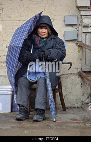Ritratto di un'anziana donna cinese con due ombrelli sul Cinese Capodanno su Mulberry Street a Chinatown, in New Foto Stock
