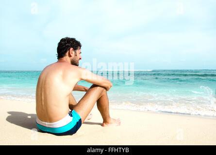L'uomo si gode della vista del mare su una spiaggia assolata. Immagine di stock