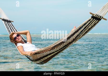 Ragazza rilassante in amaca sulla spiaggia vicino oceano blu. Bali, Indonesia. Immagine di stock. Foto Stock