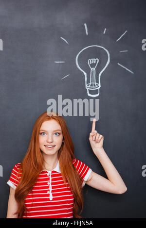 Ispirato attraente giovane donna con i capelli rossi rivolta verso l'alto ed avente un'idea su sfondo blackboard Foto Stock