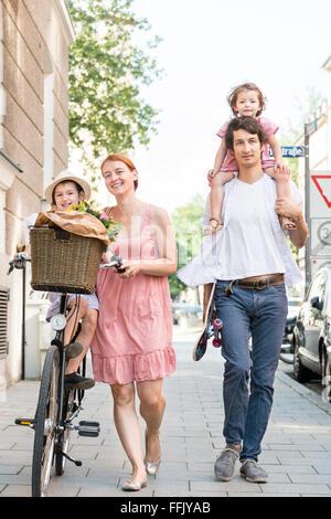Famiglia con due bambini passeggiate in città Foto Stock