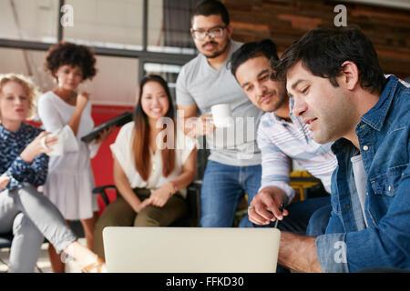 Un gruppo di giovani uomini di affari che insieme in una riunione e avente una discussione sul nuovo progetto creativo. Foto Stock