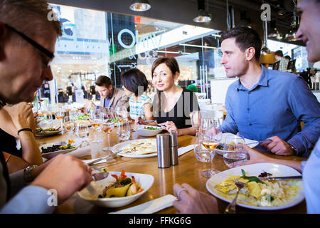 Gruppo di amici a celebrare in ristorante Foto Stock