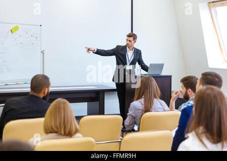 Altoparlante dando la presentazione alla conferenza di lavoro nella sala riunioni Foto Stock