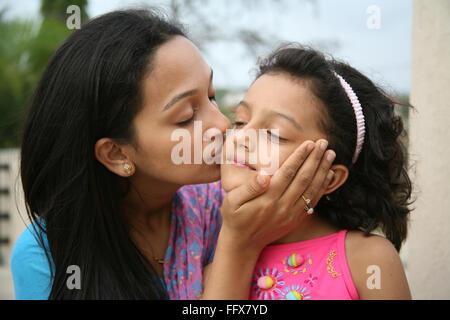 South Asian Indian madre baciare la figlia sua guancia MR3687H687E Foto Stock