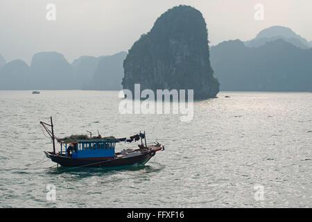 Una piccola barca da pesca motoring in un mare calmo nella baia di Halong con misty pietre calcaree carsiche dietro Foto Stock