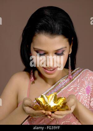 South Asian Indian donna sorridente e di colore dorato diya su mano palme signor # 702