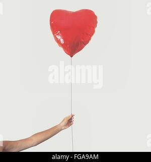 Ritagliato mano azienda cuore rosso palloncino di forma contro il cielo chiaro Foto Stock