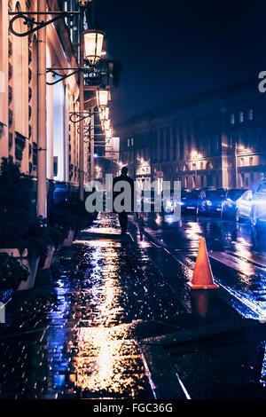 Vista posteriore del uomo a camminare sul marciapiede bagnato nella città di notte Foto Stock