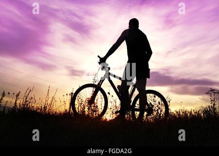 Traveler con la bici si è fermato sul campo al tramonto Foto Stock
