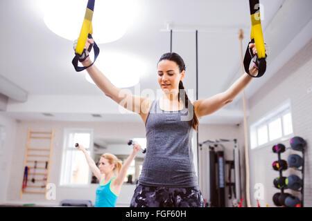Donna in palestra di formazione con bracci di trx strisce fitness Foto Stock