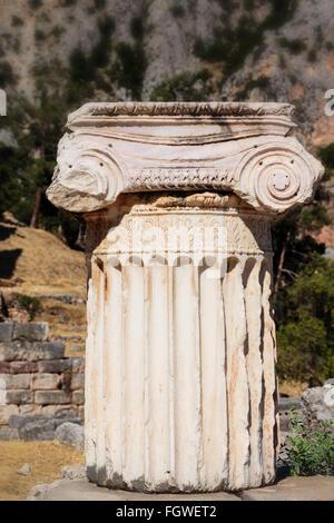 Antica Delphi, Phocis, Grecia. Colonna spezzata sulla Via Sacra coronata dal capitello corinzio Foto Stock