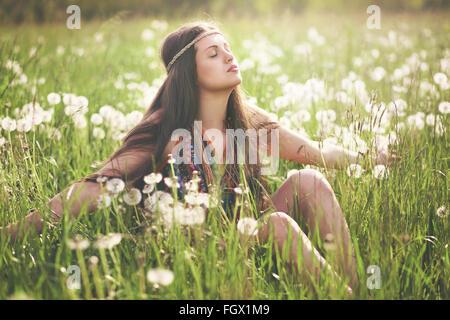 Bella donna hippie godendo della luce del sole in prato fiorito. Armonia con la natura Foto Stock
