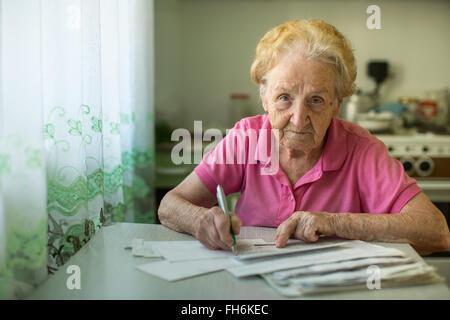 Il vecchio donna riempie le bollette seduta in cucina. Foto Stock
