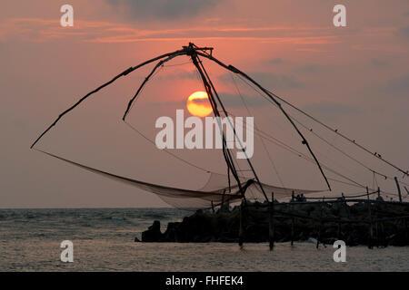 Cinese di reti da pesca stagliano dal tramonto sulla spiaggia Cherai, Vypin isola in Kerala, India Foto Stock