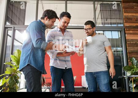Un gruppo di imprenditori per discutere dei documenti in ufficio. Tre giovani uomini riuniti in ufficio. Foto Stock