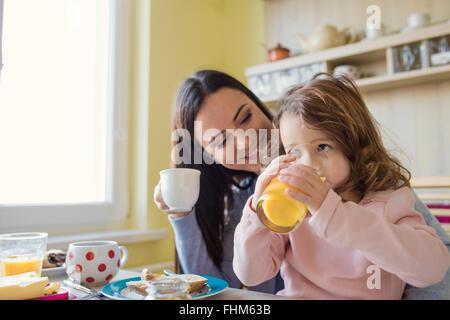 Sua madre e la sua piccola figlia insieme al tavolo per la colazione Foto Stock