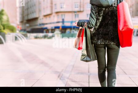 Vista posteriore della giovane donna il trasporto delle borse della spesa Foto Stock