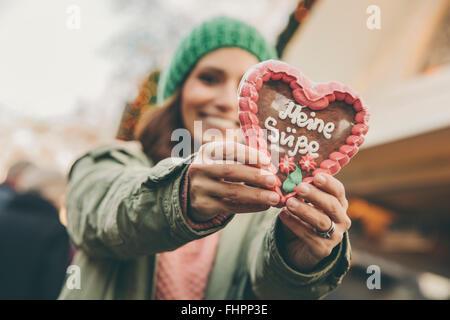 Donna che mantiene un cuore di panpepato sul mercato di Natale Foto Stock