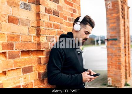 Ritratto di giovane uomo che ascolta musica con le cuffie Foto Stock