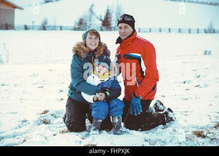 L'Italia, Val Venosta, Slingia, ritratto di famiglia sorridente nella neve Foto Stock