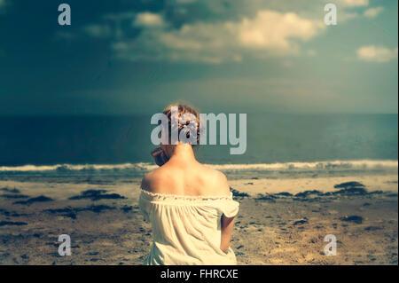 Giovane donna seduta sulla spiaggia Foto Stock
