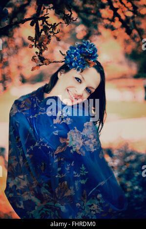 Capelli scuri giovane donna sorridente che pongono in posizione di parcheggio Foto Stock