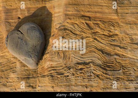 A forma di cuore dalla natura seduta in pietra sulla cima di una roccia lungo la costa. Foto Stock