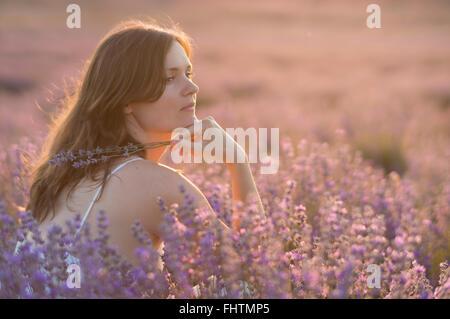 Bella giovane donna tenendo un mazzo di fiori di lavanda godendo la loro fragranza nel mezzo di un campo lanvender Foto Stock