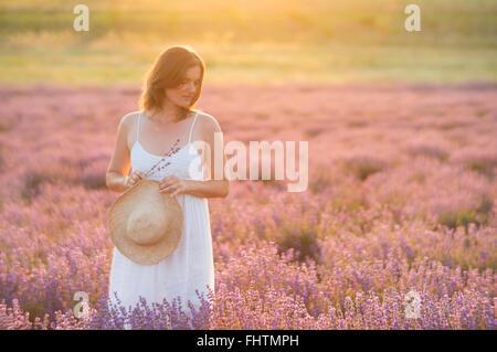Giovane e bella donna che indossa un abito bianco in piedi in un momento di pace e serenità in mezzo a un campo Foto Stock