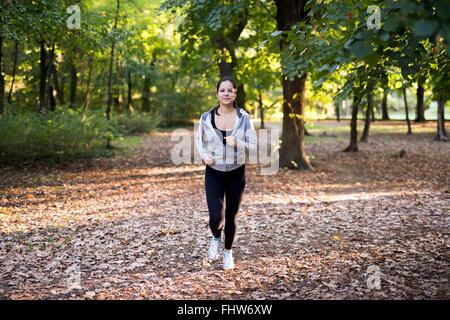 Montare la donna a fare jogging nel parco circondato da alberi verdi