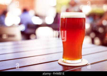 La pinta di birra predisposto su un tavolo di legno nel giardino della birra Foto Stock