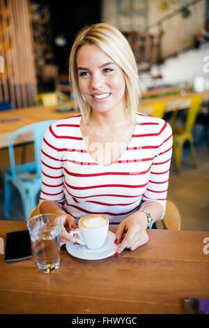 Bella donna godendo bevande nel bel cafe
