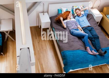 Bella giovane in appoggio sul letto in un moderno appartamento Foto Stock