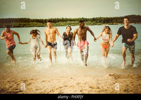 Germania, Haltern, sette amici in esecuzione mano nella mano del Lago Silbersee divertendosi Foto Stock