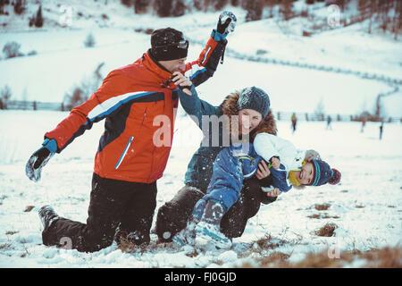 L'Italia, Val Venosta, Slingia, giocoso famiglia avente una lotta con le palle di neve Foto Stock