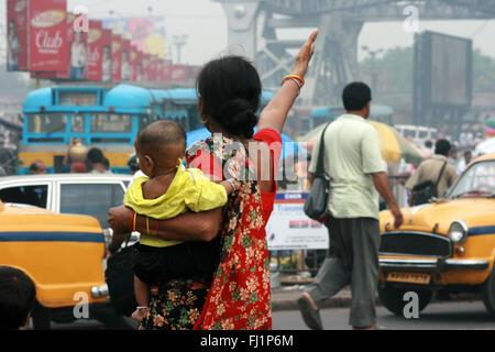 Una donna che porta il suo bambino in mezzo alla folla a quella di Howrah station di fronte a quella di Howrah bridge Foto Stock