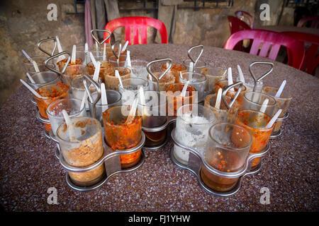 Spezie e peperoncino in bicchieri su un tavolo in un ristorante di Kampot , Cambogia Foto Stock