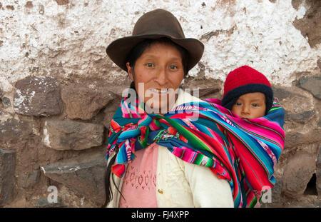 Donna in abiti tradizionali che trasportano piggyback il suo bambino in una imbracatura, ritratto, Perù, Pisaq Foto Stock