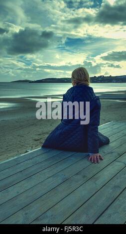 Giovane donna seduta in legno sulla spiaggia Foto Stock