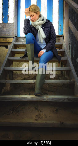 Triste giovane donna seduta sulla spiaggia di scale di cabina Foto Stock