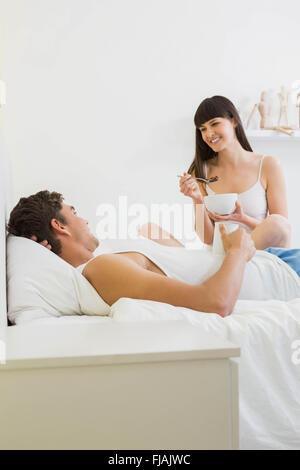 Coppia giovane avente la colazione sul letto Foto Stock