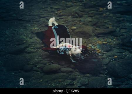 Bella donna di galleggiamento in acqua scura . Ofelia concettuale Foto Stock