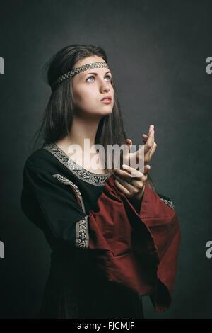 Bella donna in abiti medievali pregando con gli occhi al cielo. Storico e religione Foto Stock