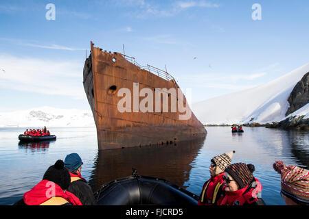 L'Antartide turismo con la nave da crociera i passeggeri in barca Zodiac visualizzazione di antico e storico della caccia alla balena nave. Foto Stock