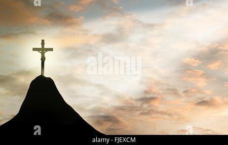 Silhouette a Gesù e la croce oltre il tramonto sulla cima della montagna